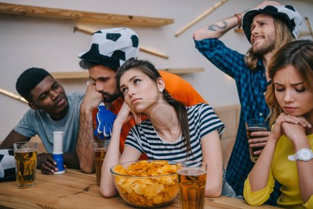 upset group of multiethnic friends in soccer ball hats watching football match at bar