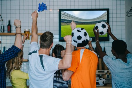 back view of football fans in soccer ball hats celebrating with hand clappers and doing yes gestures during watch of soccer match on tv screen at bar