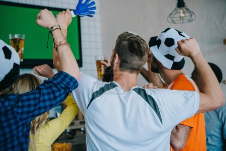 rear view of football fans in soccer ball hats celebrating with hand clappers and doing yes gestures during watch of soccer match on tv screen at bar
