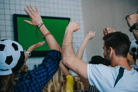 Photo pour Vue des fans de football célébrant et gesticulant de mains au cours de la veille du soccer match sur l'écran du téléviseur à arrière bar - image libre de droit