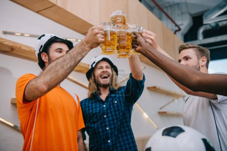 low angle view of football fans in soccer ball hats celebrating victory and clinking beer glasses at bar