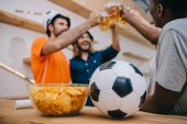 closeup view of soccer ball and bowl with chips with group of football fans celebrating and clinking by beer glasses behind at bar