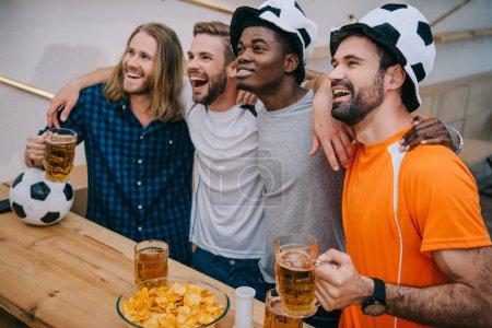 Photo pour Groupe multiculturel excité des fans de football masculin de chapeaux de ballon de football tenant bière et regarder football match à bar - image libre de droit