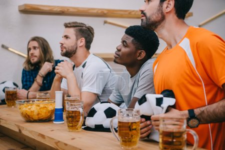 Photo pour Un groupe multiculturel de fans de football masculin avec chapeaux de ballon de soccer, de corne fan, de chips et de bière regarder football match au bar - image libre de droit