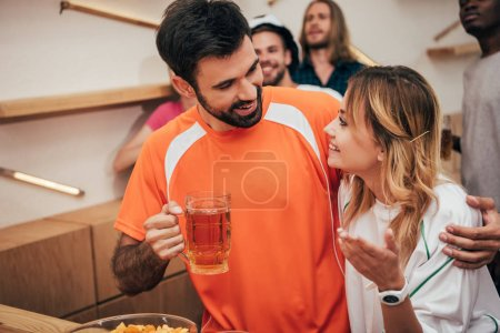 smiling man with beer embracing girlfriend and their multicultural friends watching football match at bar