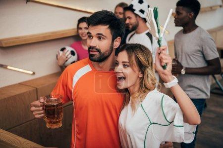Photo pour Couple et leurs amis multiculturels, regarder le football match au bar - image libre de droit