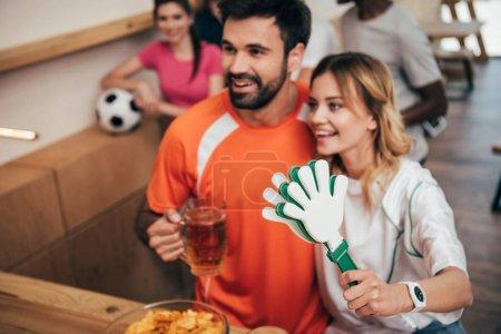 Photo pour Sourire de jeune couple avec bière et main claquettes regarder football match à bar - image libre de droit