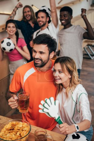 happy young couple and multicultural group of friends celebrating and gesturing during watch of soccer match at bar