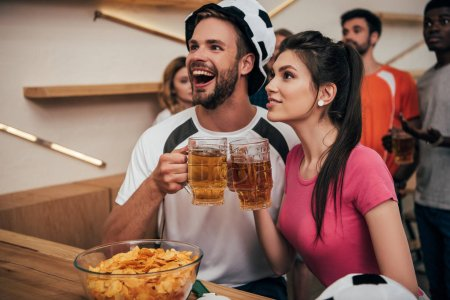 excited man in soccer ball hat clinking beer glasses with girlfriend while their multicultural friends watching football match at bar