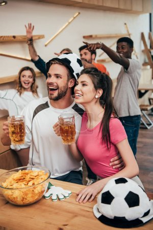 happy man in soccer ball hat embracing girlfriend and holding beer while their friends celebrating behind and gesturing by hands during watch of football match at bar