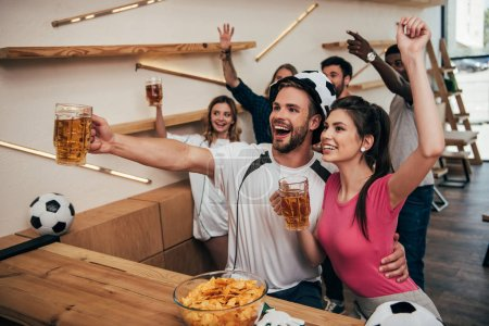 high angle view of happy man in soccer ball hat embracing girlfriend and holding beer while their friends celebrating behind and watching football match at bar