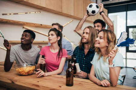 multicultural friends with football ball and hand clappers during watch of soccer match at bar