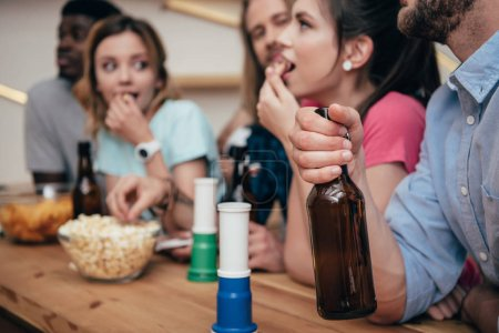 Photo for Close up view of fan horns on bar counter and group of friends with beer bottles watching soccer match - Royalty Free Image
