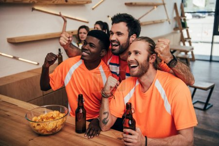 multicultural smiling friends in orange t-shirts doing yes gestures and sitting at bar with beer and chips during watch of soccer match