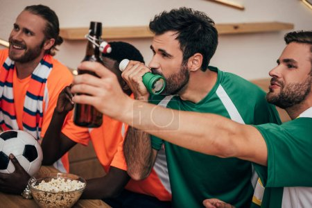 Photo pour Groupe de fans de football multiculturelle de t-shirts oranges et vertes regarder football match au bar - image libre de droit