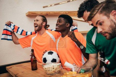 Photo pour Souriant de fans de football multiculturelle en orange, t-shirts et écharpe célébrant la victoire avec ballon tandis que leurs amis bouleversés dans différents t-shirts assis près au cours de la veille du soccer match à bar - image libre de droit