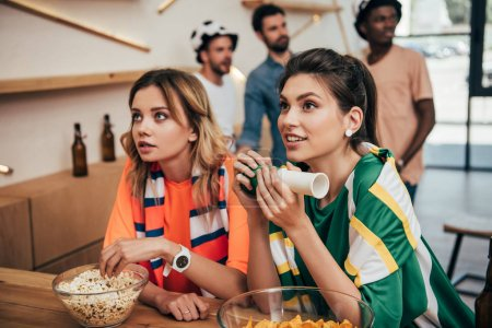 emotional young female friends in different fan t-shirts and scarfs watching soccer match at bar