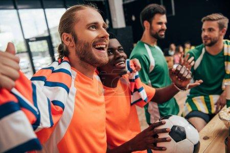 Photo pour Excité les fans de football multiculturelle en orange, t-shirts et écharpe célébrant la victoire avec ballon tandis que leurs amis bouleversés dans différents t-shirts assis derrière au cours de la veille du soccer match à bar - image libre de droit