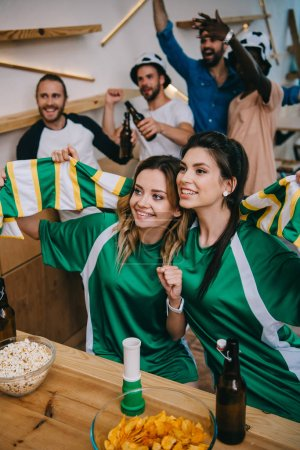 high angle view of women in green fan t-shirts holding fan scarf and their male friends standing behind during watch of soccer match at bar