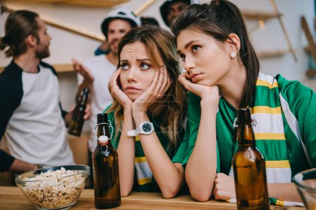 upset young women and their male friends standing behind during watch of soccer match at bar