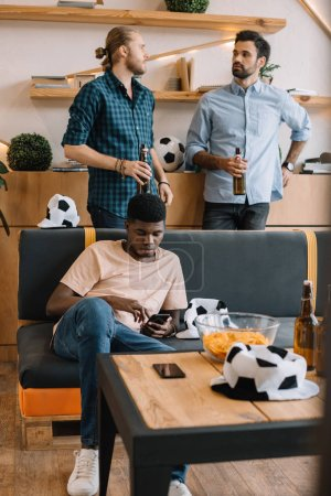 young african american man using smartphone on sofa while his friends talking with beer bottles behind at home