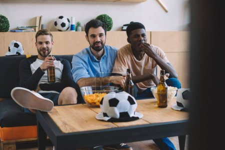 young multicultural friends watching soccer match near table with chips, popcorn and ball hats at home