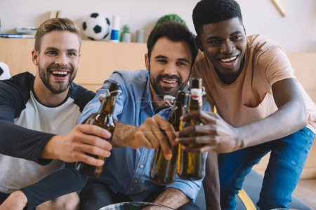 happy young multicultural friends clinking beer bottles and celebrating during watch of soccer match at home
