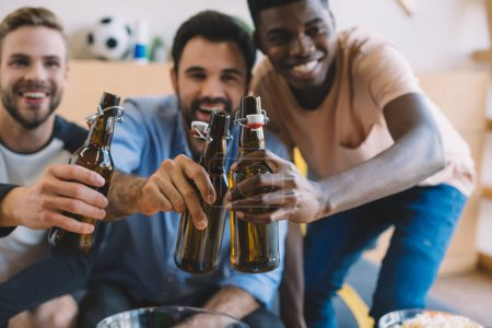 excited young multicultural friends clinking beer bottles and celebrating during watch of soccer match at home
