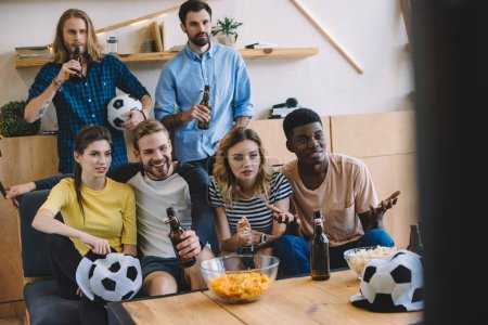 smiling multicultural friends beer bottles sitting on sofa near table with popcorn and chips watching football match at home