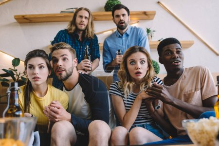 shocked group of multicultural friends sitting on sofa and watching football match at home