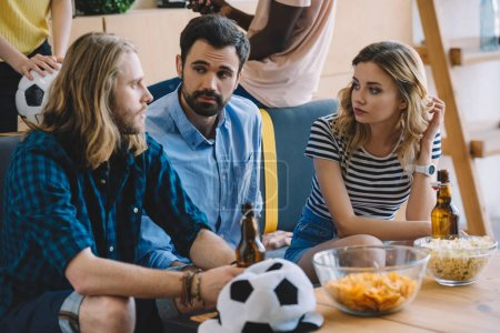 young soccer fans sitting on sofa with beer bottles and talking to each other near table with chips and popcorn