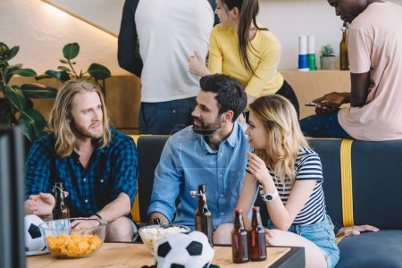 cropped image of group multicultural football fans sitting on sofa and talking to each other near table with beer, chips and popcorn