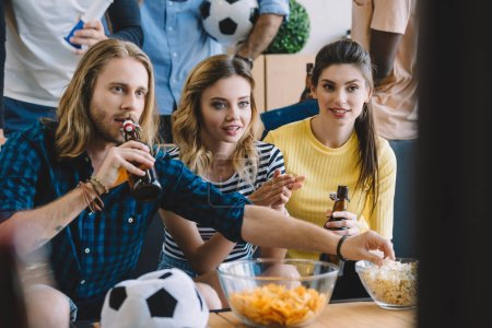 cropped shot of friends with soccer ball, beer bottles, bowls with popcorn and chips watching football match at home