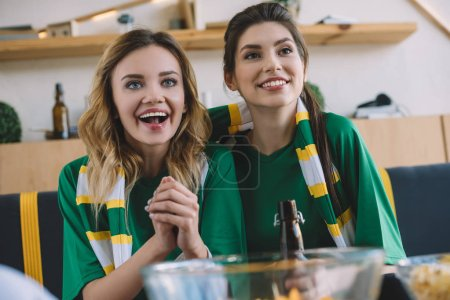 happy female football fans in green t-shirts and scarf gesturing by hands during watch of soccer match at home