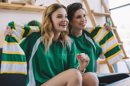 Photo for Happy female football fans in green t-shirts and scarf gesturing by hands during watch of soccer match at home - Royalty Free Image