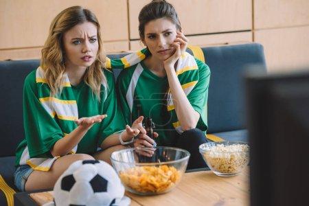 Photo pour Deux bouleversé les fans de football féminin en vert t-shirts et écharpe gesticulant de mains au cours de la veille du match de football à la maison - image libre de droit