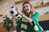 young excited female football fan in green t-shirt and scarf holding ball and celebrating during watch of soccer match at home