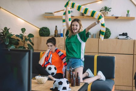 excited woman in green fan t-shirt celebrating victory and holding scarf over head while her upset female friend in orange t-shirt sitting near on sofa during watch of soccer match at home