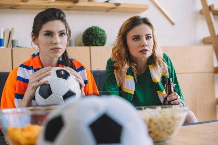 Photo pour Axé sur les fans de football féminin en différents t-shirt et écharpes regarder football match à la maison - image libre de droit