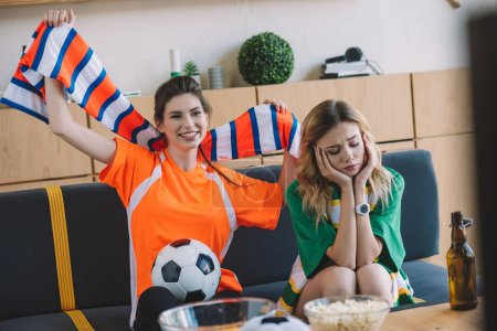 happy woman in oarnge fan t-shirt celebrating victory and holding scarf over head while her upset female friend in green t-shirt sitting near on sofa during watch of soccer match at home