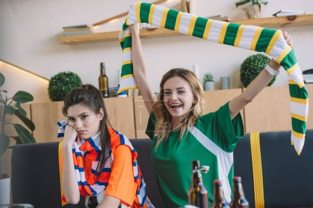 smiling woman in green fan t-shirt celebrating victory and holding scarf over head while her upset female friend in orange t-shirt sitting near on sofa during watch of soccer match at home