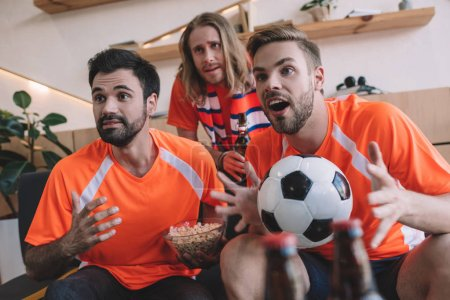 emotional young male football fans in orange t-shirts with ball and popcorn watching soccer match at home