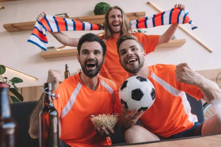 excited young male football fans in orange t-shirts with scarf, ball and popcorn celebrating and watching soccer match at home