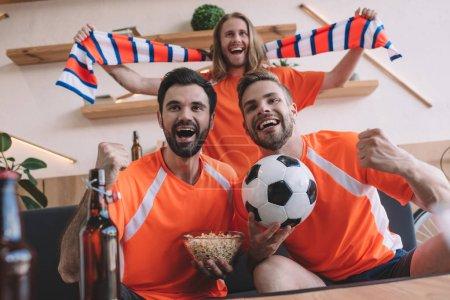 Photo pour Heureux les fans de football masculine jeune dans des t-shirts orange avec foulard, boule et popcorn célébrant et regarder football match à la maison - image libre de droit