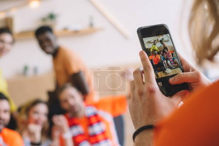 cropped shot of man taking picture of friends on smartphone at home
