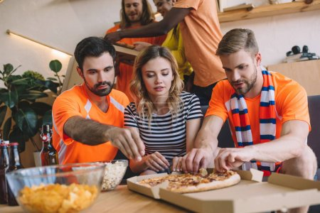 group of friends taking pizza slices from box on table at home