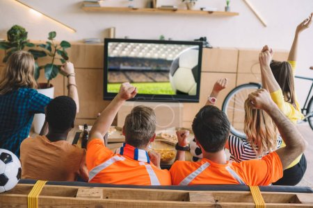 rear view of group of friends celebrating and doing yes gestures while sitting on sofa during watch of soccer match at home