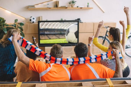 group of football fans celebrating and doing yes gestures while sitting on sofa during watch of soccer match at home