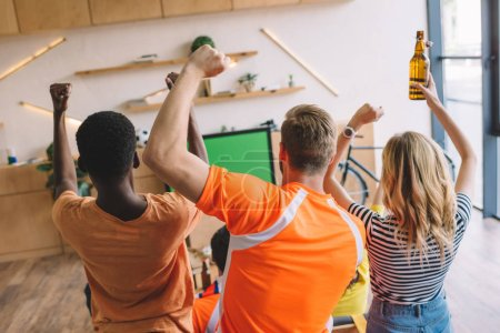 high angle view of group of friends celebrating and doing yes gestures while watching soccer match at home