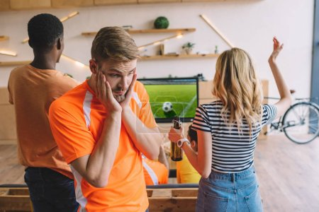 frustrated young man with hands on cheeks and his friends watching soccer match on tv screen at home